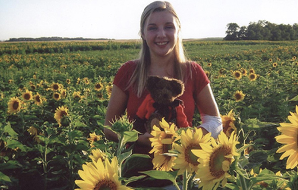 14 year-old Ashlee Rudolf stands in a field of North Dakota sunflowers with Burke P. Bear. Ashlee's family hosted Burke P. Bear in North Dakota.